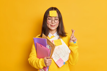 Pleased Asain female student believes in good luck at exam stands with eyes closed and fingers crossed believes dreams come true stuck with papers holds folders isolated over yellow background