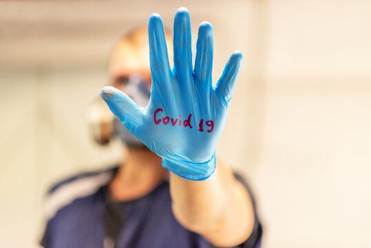 Young man in a protective medical mask and latex gloves holds her hand and shows the viewer on a light isolated background.