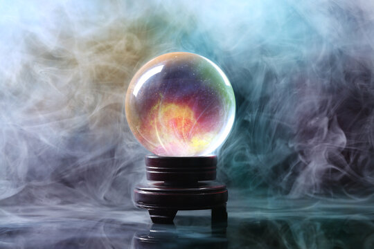 Crystal ball of fortune teller in smoke on table