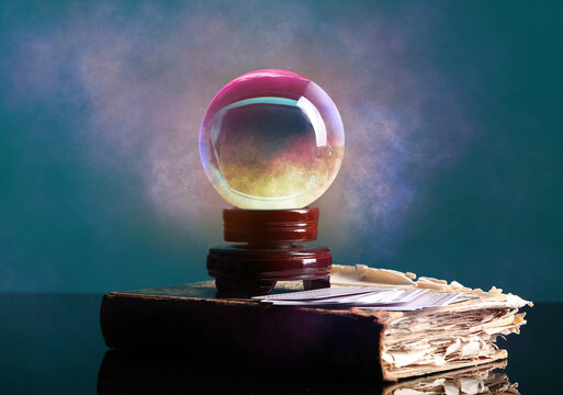 Spell book, crystal ball of fortune teller and cards on table
