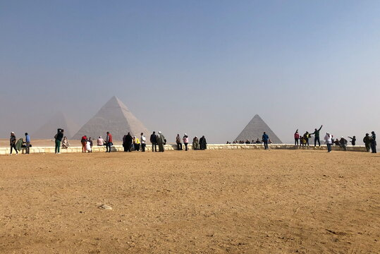 Visitors gather to look at the Great Pyramids of Giza, in Giza