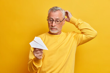 Serious hesitant grey haired man plans his business trip looks confused at handmade paper plane scratches head wears glasses casual jumper poses against yellow background. People age ambitions