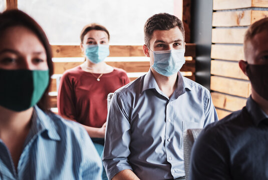 Young people in the new normal wearing masks on their faces are listening to the coach - Millennials are learning from the coronavirus epidemic - Meeting in the auditori hall