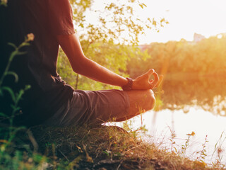 A young man in a lotus position on the bank of a river at sunset. Close-up
