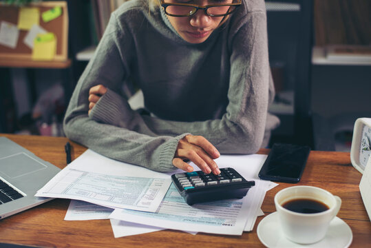 Season to pay Tax, Budget, and Tax planning concept. Business woman wear glasses calculating annual tax and using mobile phone. Calendar 2021 and personal income tax form placed on home office desk.
