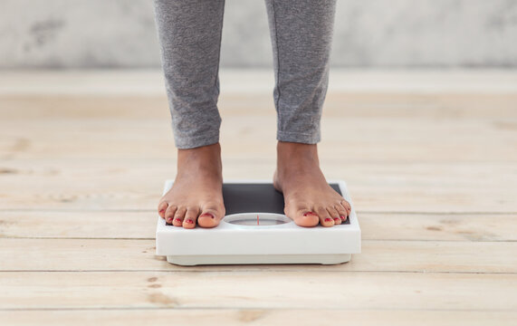 Closeup of young African American woman standing on scales indoors, checking her weight, cropped view of feet