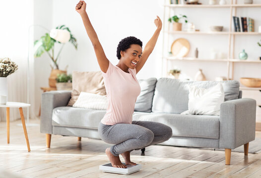 Young black woman sitting on scales, raising hands up in excitement, happy with result of her weight loss diet at home