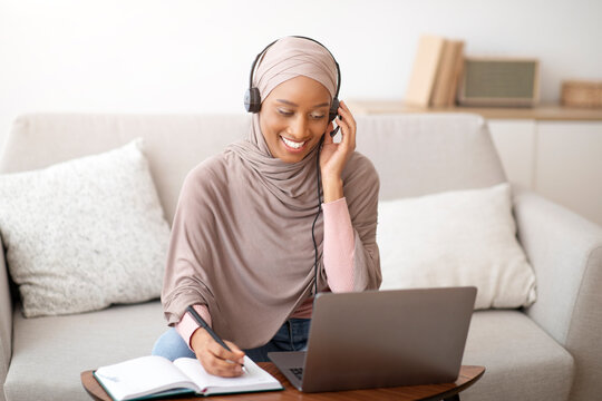 Joyful African American woman in hijab and headphones taking notes during online business meeting on laptop at home