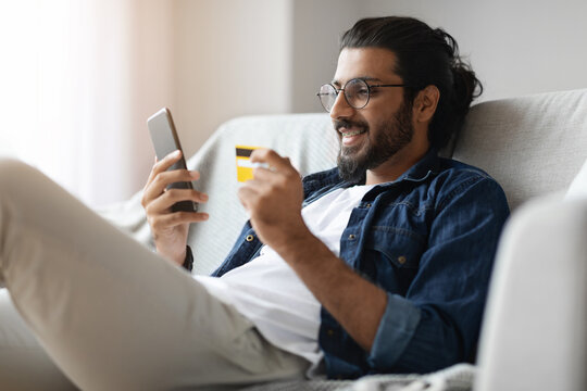 Cheerful Arab Guy Shopping Online With Smartphone And Credit Card At Home
