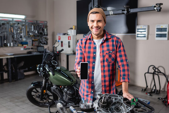 cheerful mechanic showing mobile phone with blank screen near spare parts and motorcycle in workshop