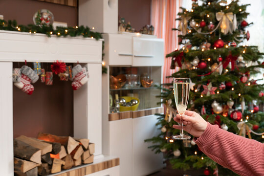 Christmas tree stands in modern living room. A woman holds a glass of champagne in her hand. In the background is an electric fireplace.