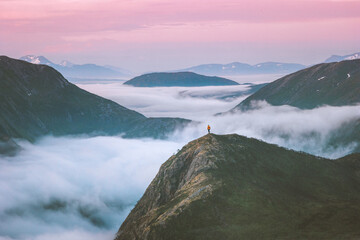 Traveler hiking above mountain clouds enjoying Norway sunset landscape travel adventure lifestyle vacation outdoor epic trip