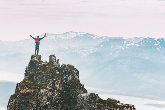 Man climbing on mountain top adventure travel outdoor extreme active lifestyle vacation tour hiking in Norway success raised hands Husfjellet peak