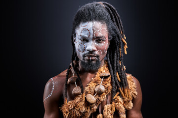 Fototapeta african shirtless guy with colourful make-up isolated on dark studio background, young male tribal has ethnic traditional chain