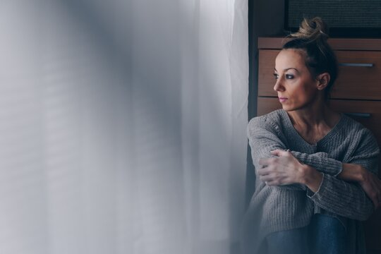 Beautiful sad woman sitting on the floor looking at the window. Depression and despondency.