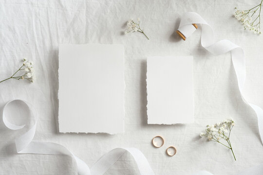 Blank wedding invitations cards mockups with space for text, golden rings, ribbon flowers on white textile background. Flat lay, top view.