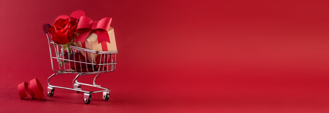 St. Valentine's Festive sale concept banner with gift box rose, and red paper hearts in the shopping cart against a red background.