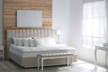 Comfortable bed with soft white pillows indoors