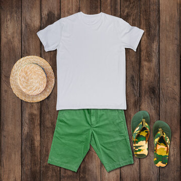 White t-shirt with green shorts, sandals, hat placed on the wooden floor.
