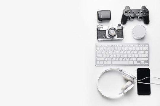 Composition with computer keyboard and different modern devices on white background