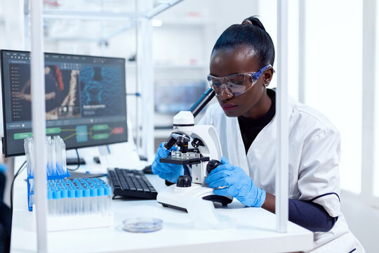 African researcher adjusting microscope lenses looking at sample on glass slide. Black healthcare scientist in biochemistry laboratory wearing sterile equipment.