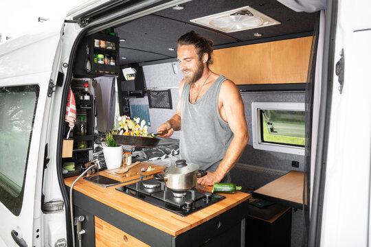 Smiling man cooking inside his camper van