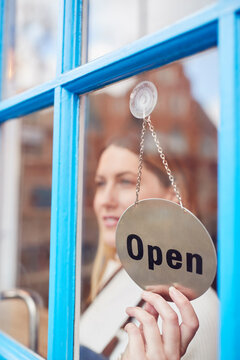 Female Small Business Owner Turning Around Open Sign On Shop Or Store Door