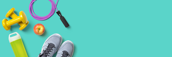 Fitness equipment on a turquoise background with copyspace