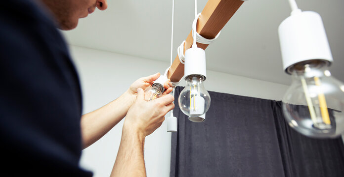 The electrician is installing the led light bulbs into the chandelier