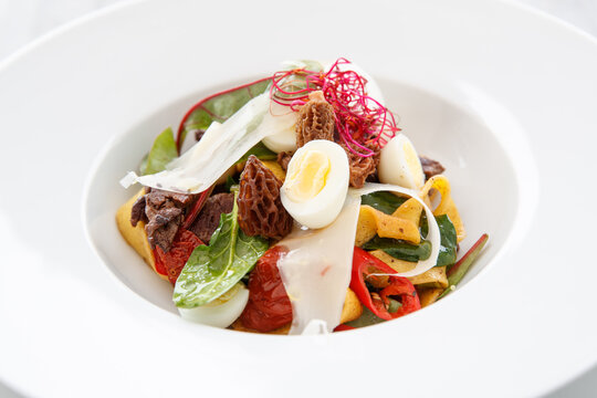 Salad with wide noodles and small egg