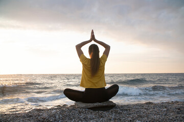 Yoga woman in Lotus position practicing yoga and meditation. outdoors on the evening ocean