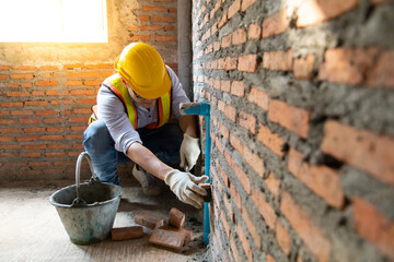 Fototapeta Man bricklayer installing bricks on construction site obraz