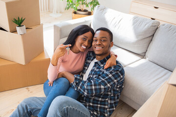 Black millennial lady with her husband hugging and holding house key in their new property
