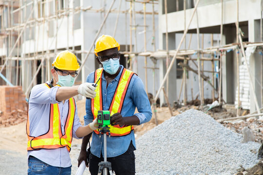 African american foreman and Asian man worker in safety hard hat helmet working together on construction site. wearing surgical face mask during coronavirus covid and flu outbreak