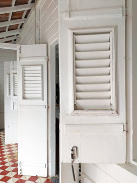 Perspective view of white wooden shutters and storm doors in traditional Caribbean colonial house. Architecture and construction pattern. Old wooden beams painted white.