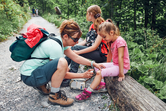 Mother dressing the wound on her little daughter's knee with medicine in spray. Accident happened during family summer vacation trip. People actively spending time