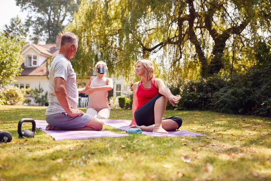 Senior Couple Taking Part In Private Socially Distanced Yoga Class With Teacher At Home