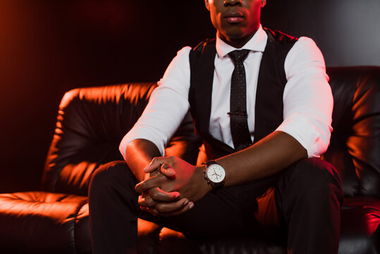 cropped view of african american man in suit sitting on sofa with clenched hands on black background