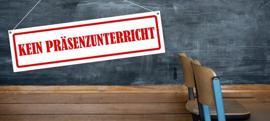 CORONAVIRUS: Schild mit den Worten: KEIN PRÄSENZUNTERRICHT, alte Schultafel und alte hochgestellte...