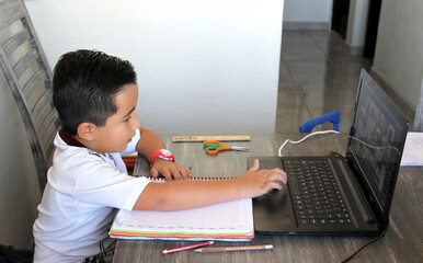 back to school, 7 year old Latino boy in online home classes with laptop and school supplies