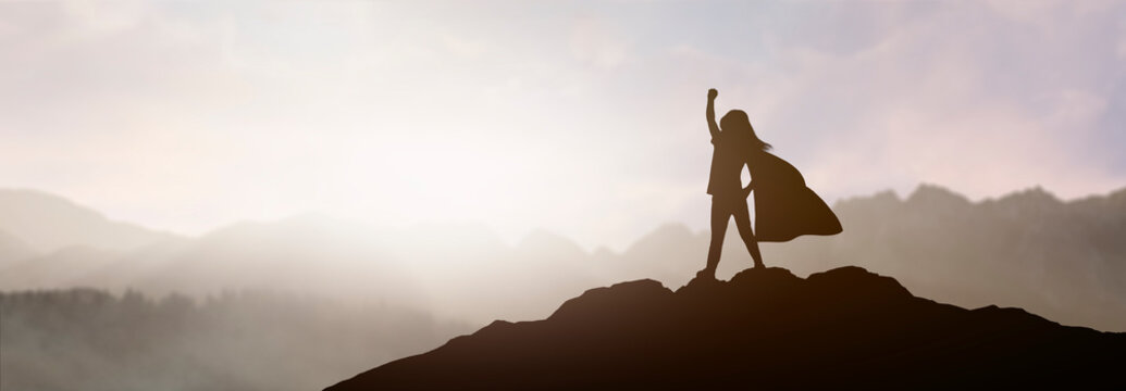 silhouette of a girl who dreams of being a superhero in a beautiful mountain landscape with a raised fist