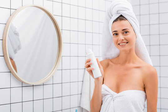 cheerful woman looking at camera while holding deodorant in bathroom near mirror