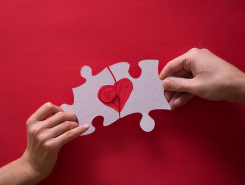 Hands holding jigsaw puzzle with red heart connecting completed, success, love and healthcare concept
