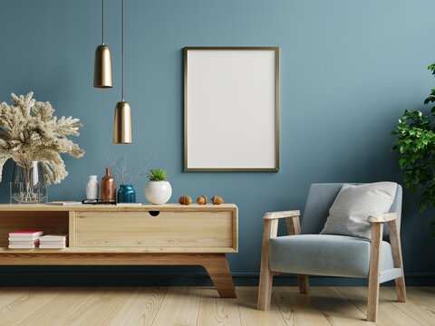 Poster mockup with vertical frames on empty dark green wall in living room interior with blue velvet armchair.