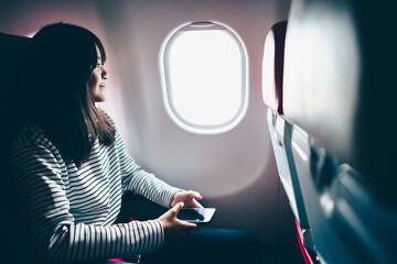 Teenage girl looking out of airplane window