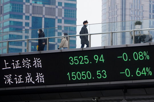 People wearing masks, following the coronavirus disease (COVID-19) outbreak, walk on an overpass with an electronic board showing Shanghai and Shenzhen stock indexes, at the Lujiazui financial district in Shanghai