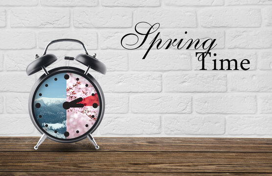 Alarm clock on table against white brick background with text SPRING TIME. Concept of time change