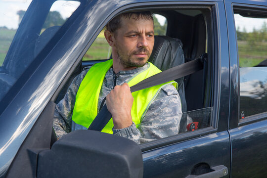 A 40-year-old man wearing a seat belt in a car.