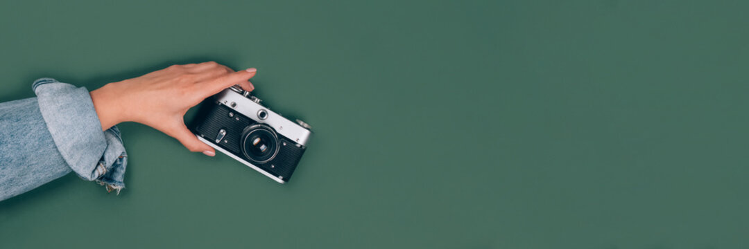 Banner with female hand holding old retro photo camera on green background with copy space for text. Trendy vintage photography, Online photography school concept, selective focus