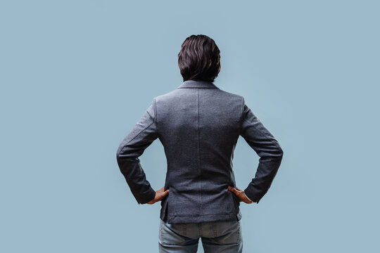 The businessman in his jacket folded his hands on his belt. Rear view. On a blue background.